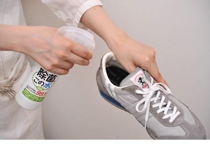 靴の中に微酸性電解水を噴霧している写真